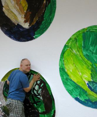 der Künstler vor seinen Malereien