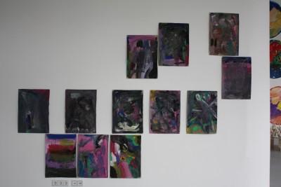Eine Bildinstallation, die aus abstrakten zwar bunten und eher dunklen Bildern besteht.