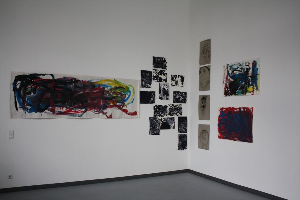 Eine weitere Bildinstallation in der Ecke der Galerie. Sie besteht aus bunten und schwarz-weißen Bildern, sowie Kohlezeichnungen von Gesichtern.