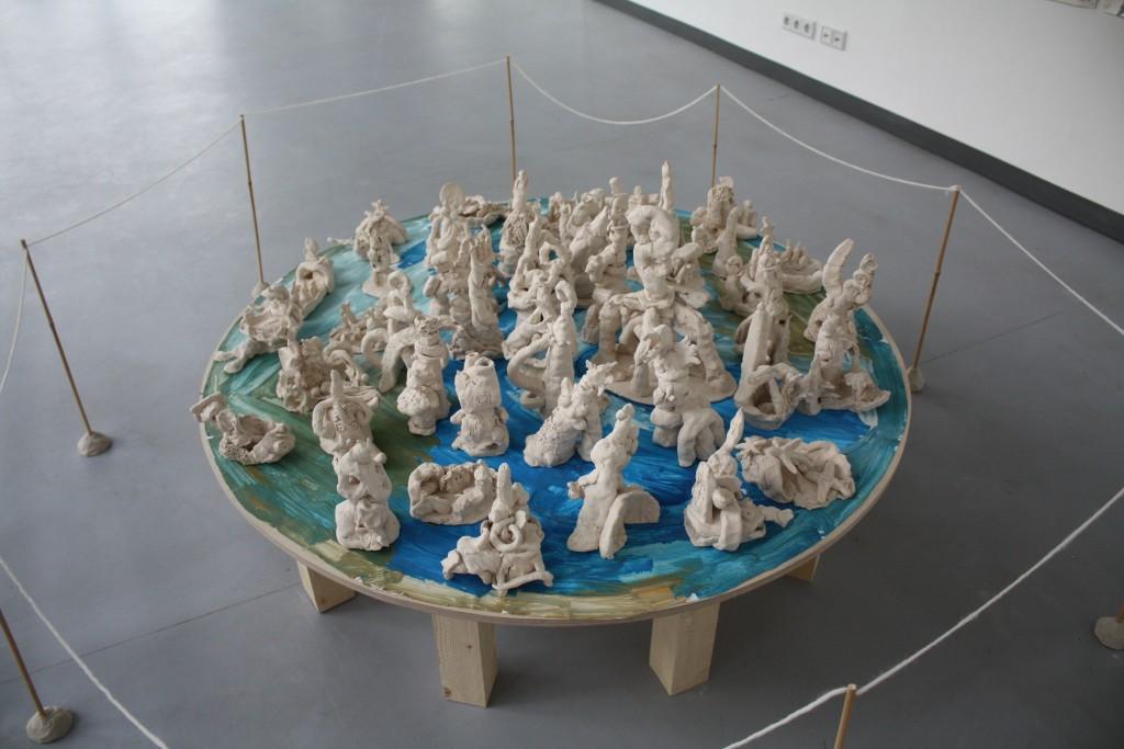 Draufsicht auf einen kleinen, runden Holztisch mit Figuren aus weißer Modelliermasse.