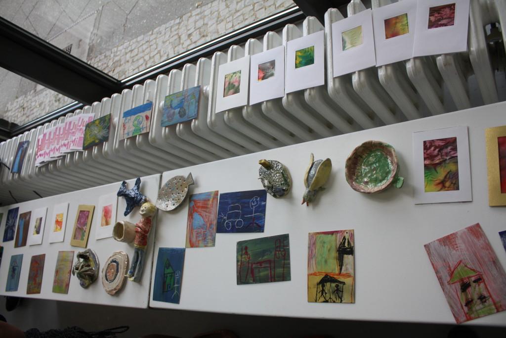 Die einzelnen Bilder und Tonskulpturen der Kinder wurden für die Betrachter auf einer Tischreihe entlang der Fensterfront der Gallerie aufgestellt.