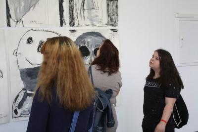 Drei Besucherinen betrachten die Bildinstallation mit den Zeichnungen der Kinder.