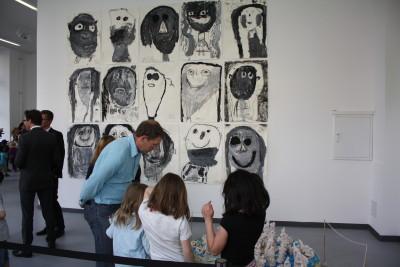 Drei Mädhen zeigen einem Besucher die von ihnen angefertigten Figuren.
