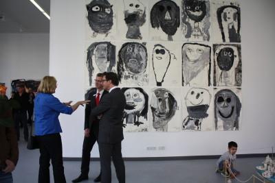 Sabine Weißler, Bezirksstadträtin für Weiterbildung, Kultur, ist mit zwei Herren in ein Gespräch vertieft. Im Hintergrund sieht man eine Bildinstallation, welche aus einzelnen Kohlezeichnungen der Kinder zusammengestellt wurde.