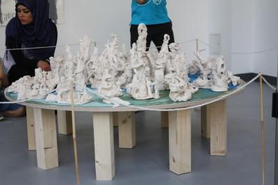 Von den Kindern aus weißer Masse modellieren Figuren wurden auf einem runden Holztisch in der Galerie aufgestellt.