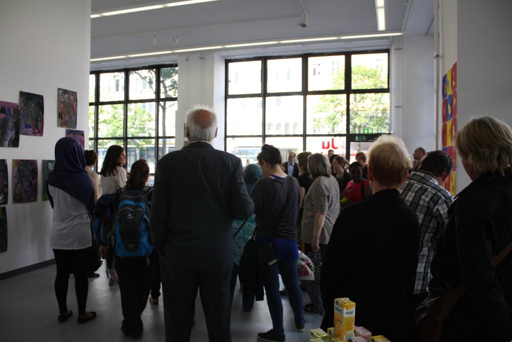 Die zahlreichen Besucher stehen im Vordereraum der Galerie und lauschen den einführenden Worten.