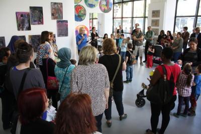 Sabine Weißler, Bezirksstadträtin für Weiterbildung und Kultur, begrüßt die Eltern der Kinder und weitere Besucher der Ausstellung in der Gallerie Wedding.
