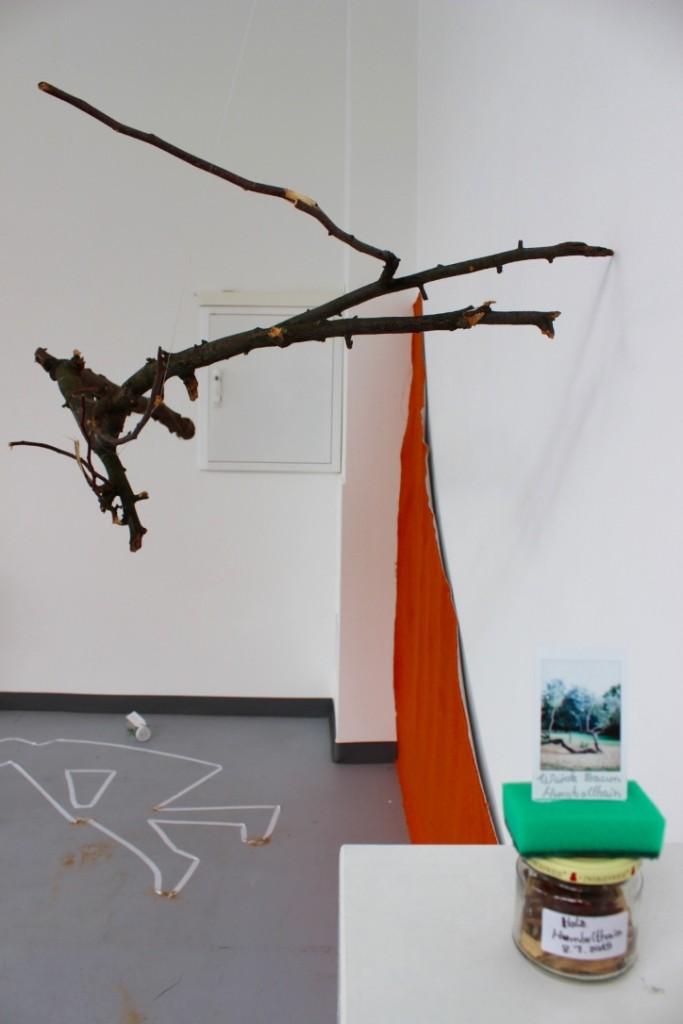 Ein Blick in die Ausstellung des Projekts. Kinder erstellten in Zusammenarbeit mit Künstlern Werke aus verschiedenen auch gesammelten Materialien. Hier z.B. eine Installation mit einem Ast, einem Stück orange bemalter Pappe sowie ein befülltes Glass mit Schwamm und einem Foto oberhalb des Deckels.