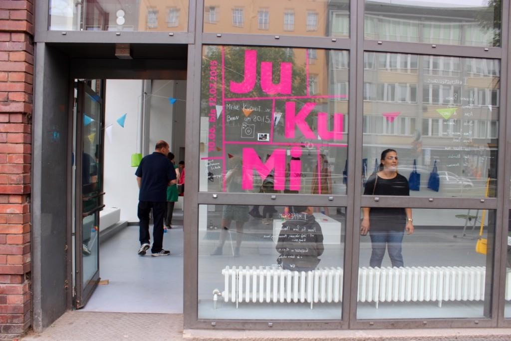 Selbst die Fensterfront wird durch Aufschriften in die Ausstellung integriert. Eine Besucherin betrachtet diese gerade.