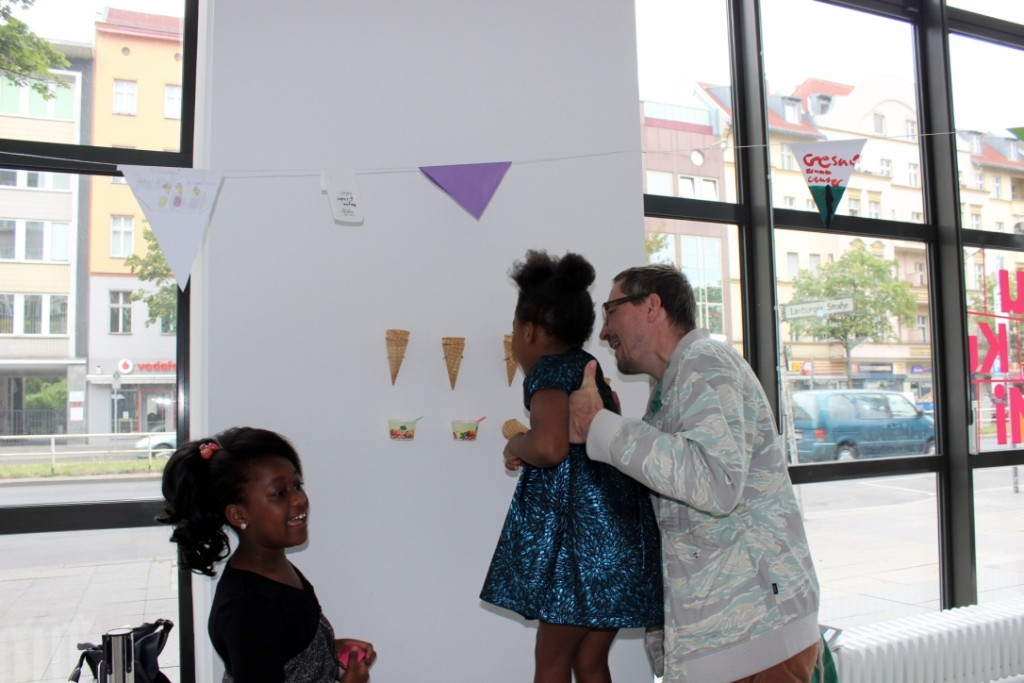 Ein Besucher hält ein Mädchen in den Händen und hilft ihr die Eiswaffel-Installation zu betrachten. Ein weiteres Mädchen steht daneben und redet.