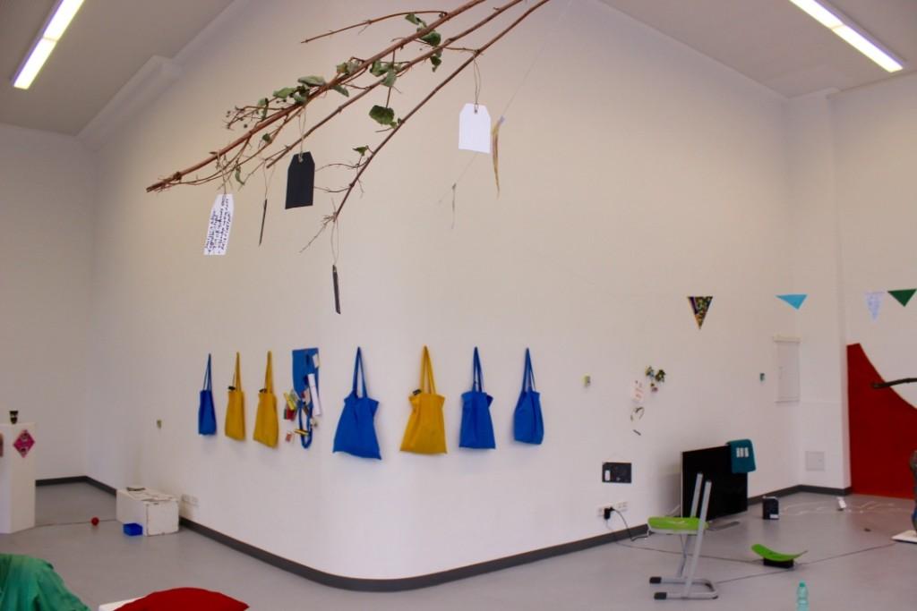Eine Installation besteht aus befüllten blauen und gelben Taschen, welche an einer der Galeriewände aufgehängt wurden.