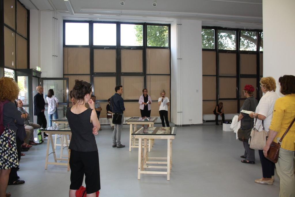 Die den Ausstellungsrundgang führende Kuratorin spircht zu den im vorderen Teil der Galerie verteilten Besuchern.