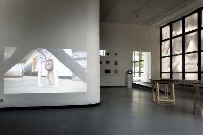 Einen Teil der Ausstellung bildet eine audiovisuelle Installation im vorderen Teil des Raumes, welche auf eines der weißen Galeriewände projiziert wird.
