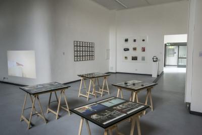 In der Nähe des Eingangs befinden sich vier Holztische mit schwarzen Platten und auf ihnen ruhenden Bildern.