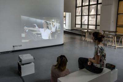 Zwei Besucherinen betrachten mit aufgesetzten Kopfhörern die audiovisuelle Installation.