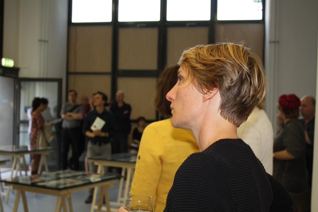 Eine Besucherin im Vordergrund folgt konzentriert der Ausstellung.