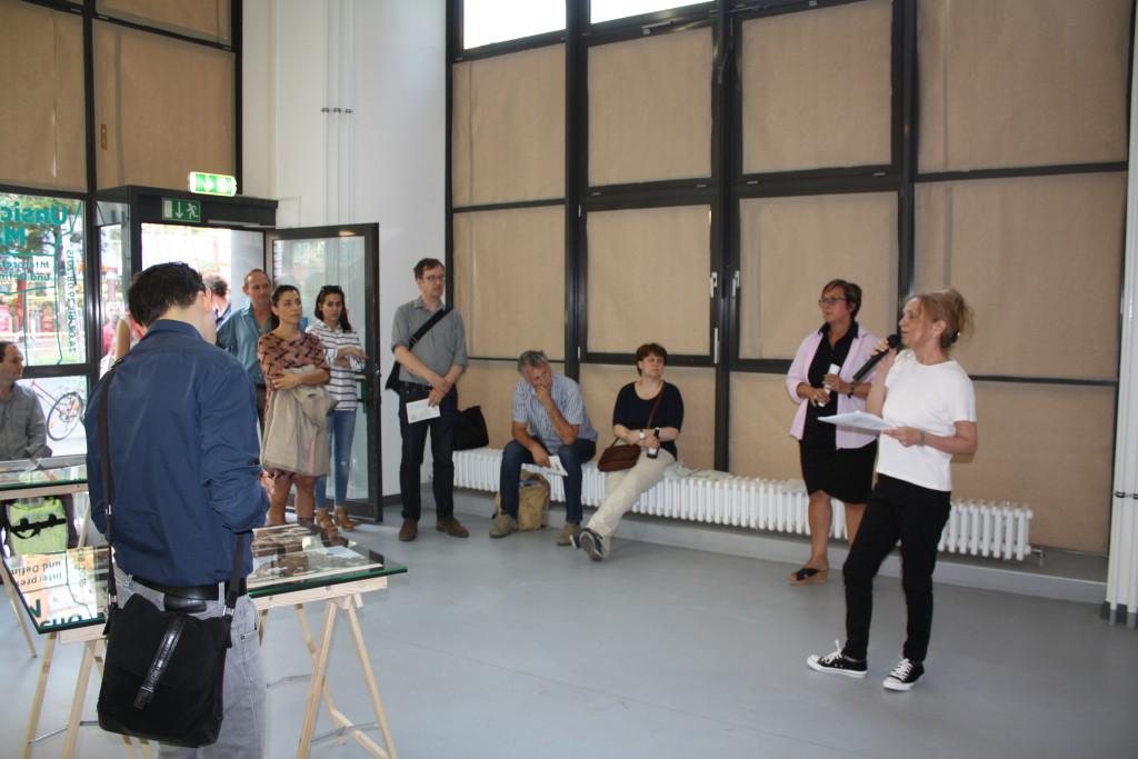 Die sich in der Galerie gerade einfindenden Besucher hören den Schiderungen der Kuratorin Sabine Winkler zu.