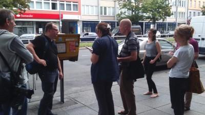 Die Teilnehmer betrachten einen Briefkasten, tauschen sich darüber aus und machen Notizen.
