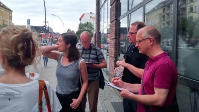 Bereits vor der Galerie findet ein reger Austausch zwischen den Beteiligten statt. Zwei Teilnehmer machen Notizen.