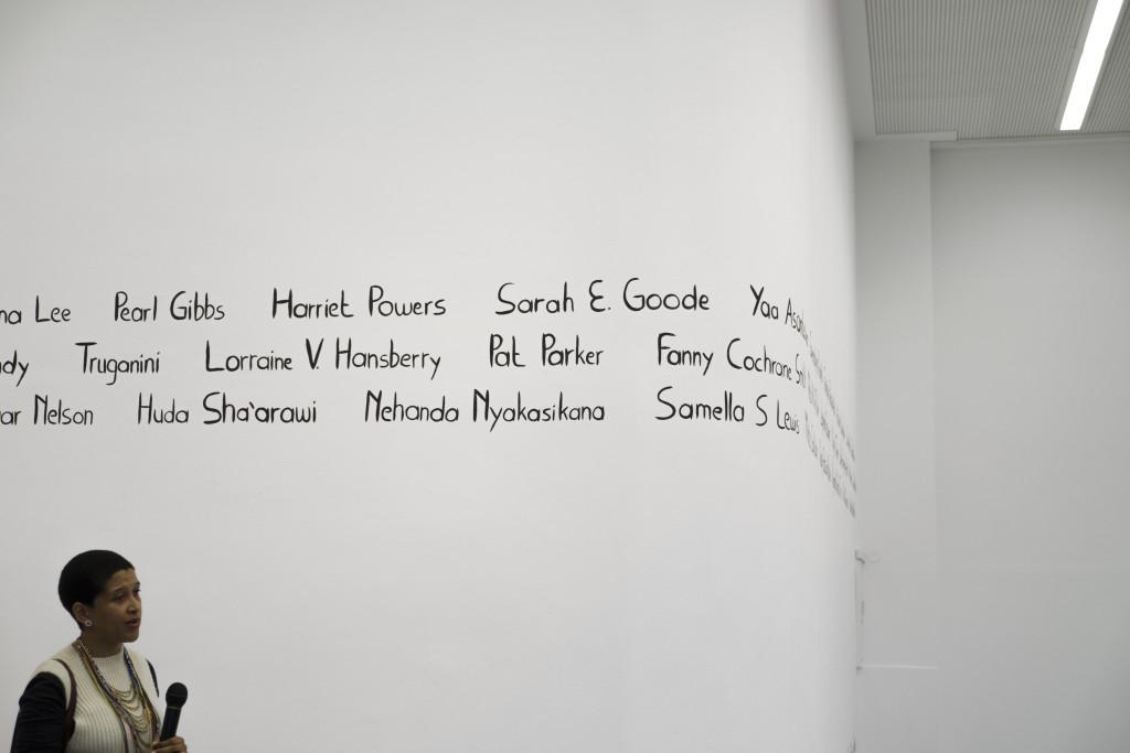 Die Künstlerin steht vor der Wand mit den aufgemalten Frauennamen und führt Erläuterungen aus, ein Mikrofon in der Hand haltend.