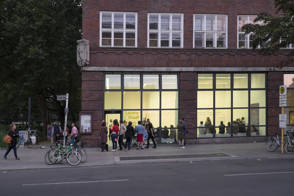 Ein Blick auf die Fensterfassade der Galerie Wedding, mit den sich in sowie vor der Galerie versammelnden Ausstellungsbesuchern.