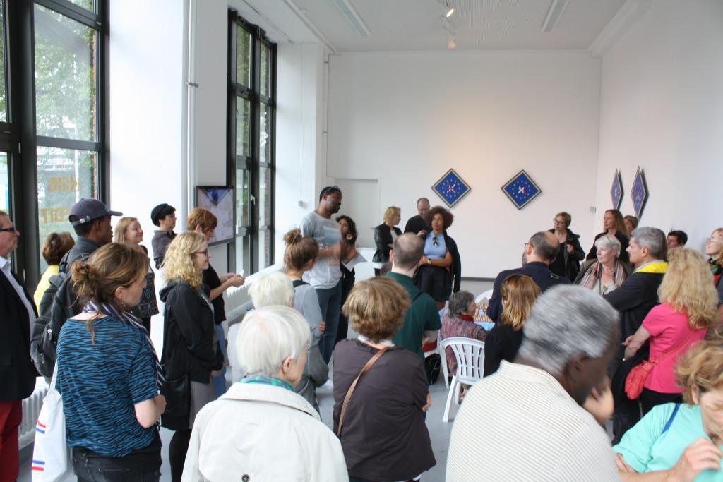 Der Künstler steht im vorderen Teil der Galerie von Besuchern umgeben, welche konzentriert seinen Ausführungen lauschen.