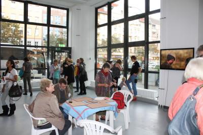 Während einige Besucher noch die Ausstellung betrachten, unterhalten sich die anderen bereits miteinander.