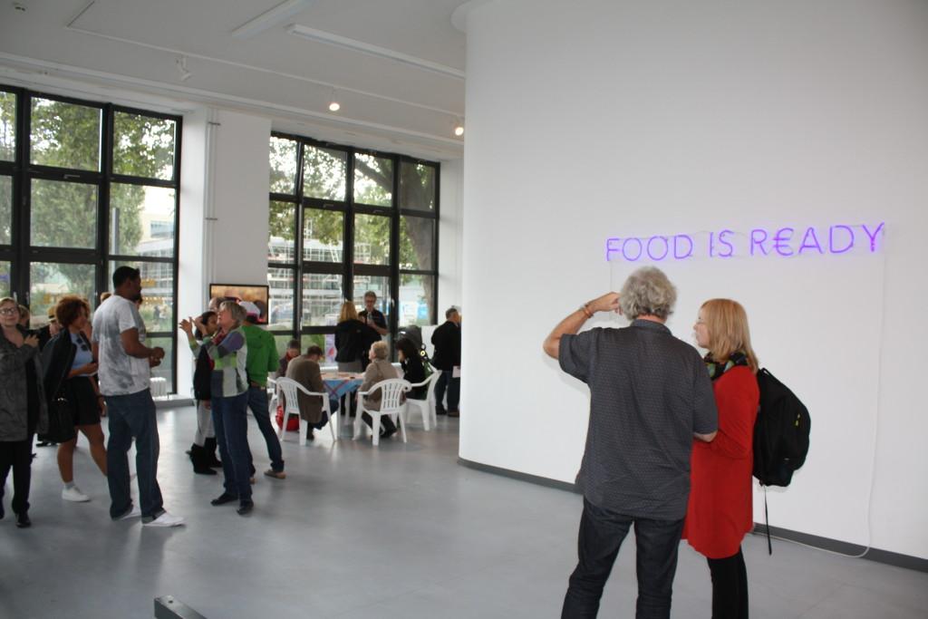 Die Besucher versammeln sich in der Galerie zum Artist-Walk mit Emeka Ogboh. Einige bilden eine Gruppe um den Künstler und lauschen seinen Gespräch mit einer Frau, die vor ihm steht.