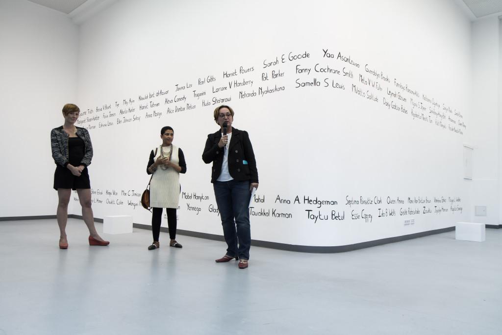 Die Kuratorin Solvej Helweg Ovesen, die Künstlerin Lerato Shadi und die Leiterin des Bildung-und-Kultur-Bereichs Ute Müller-Tischler stehen zusammen vor einer der Galeriewände. Frau Müller-Tischler spircht ein paar Worte zur Ausstellungseröffnung.