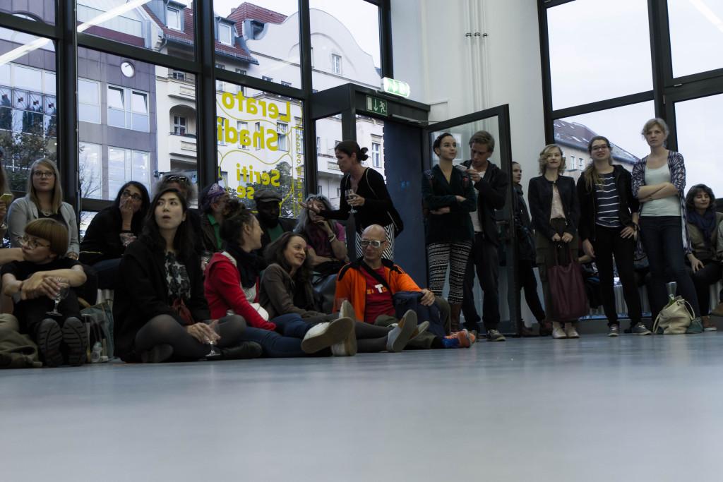 Zahlreiche Besucher versammeln sich im der Galerie vor den verglasten Wänden und verfolgen konzentriert die Performance.