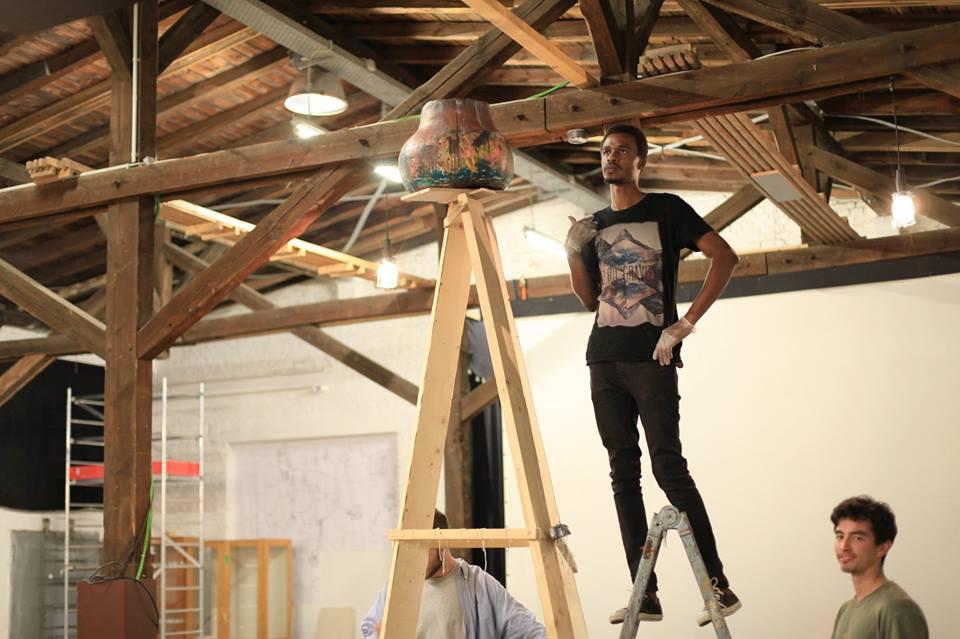 Der junge Kurator Folakunle Oshun steht auf einer Leiter vor einem Holzgerüst und betrachtet das dort auf der Spitze plazierte Tongefäß.