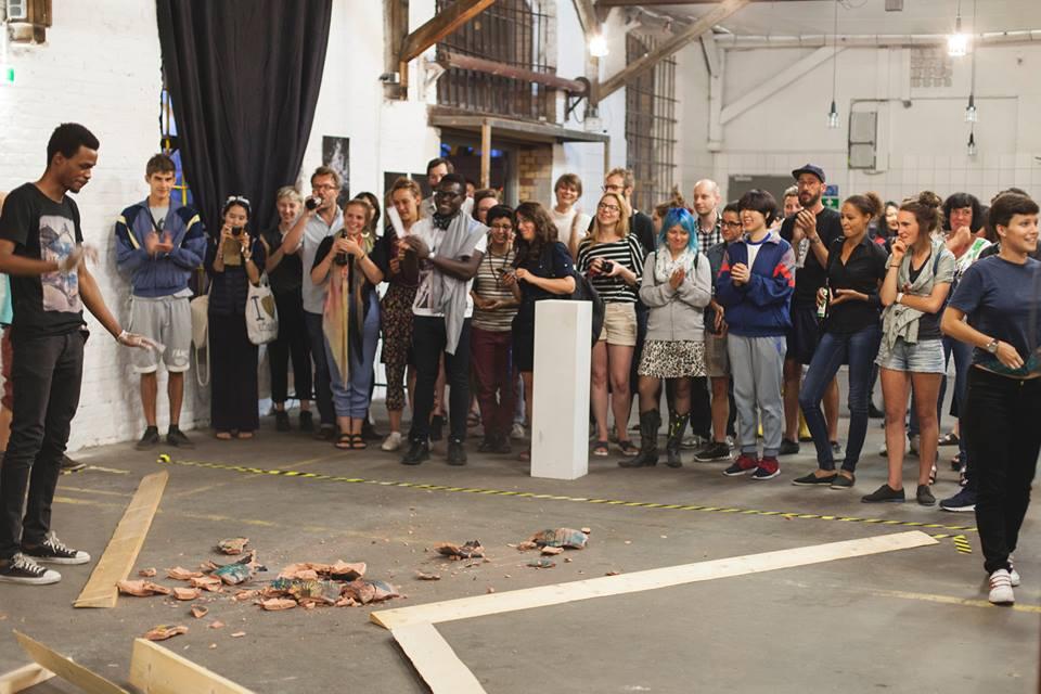 Direkt nach der Performance steht der Kurator vor den Scherben und das Publikum applaudiert.