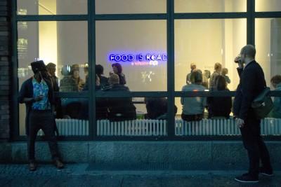 Zwei Personen betrachten das Innere der Galerie, sowie die Lichtinstallation über die Glasfassade.