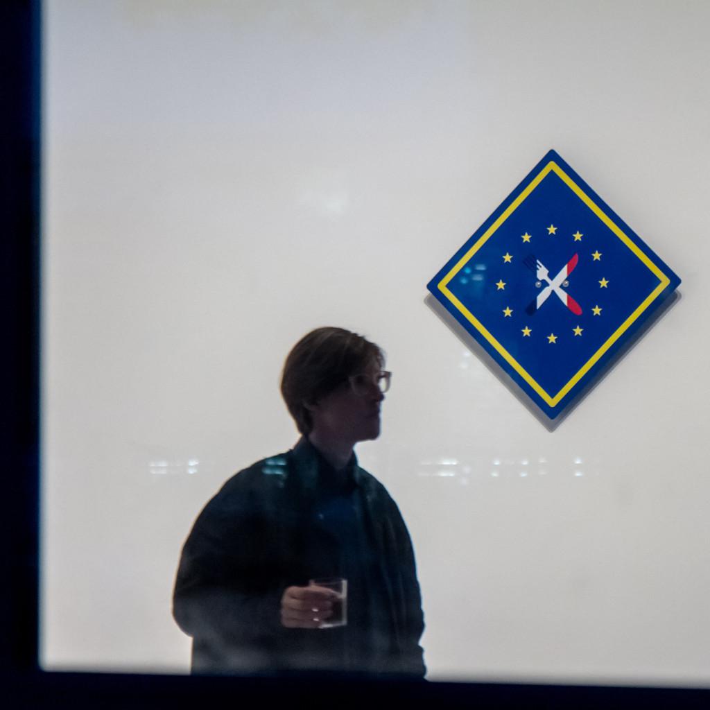 Ein Ausstellungsbesucher betrachtet eine Objektinstallation an der Wand.