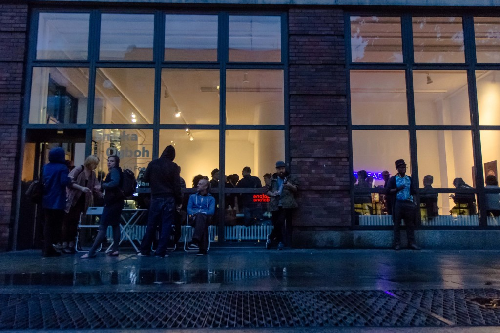 Ein Blick auf die Glasfassade der Galerie mit den davorstehenden Besuchern, sowie der Ausstellungseröffnung innen.