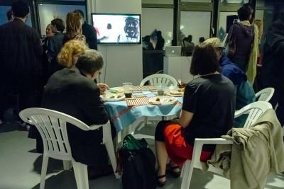 Eine kleine Gruppe von Besuchern isst beim Tisch, welcher zusammen mit mehreren Stühlen zu den ausgestellten Kunstwerken gehört, und schaut einen Film, der ebenfalls einen Teil der Ausstellung bildet.