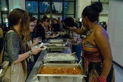 Die Ausstellungsbesucher stellen sich vor einem Buffet mit afrikanischen Speisen auf, welche ihnen durch zwei junge Frauen gereicht werden. Eine davon trägt ein Kleid im afrikanischen Stil.