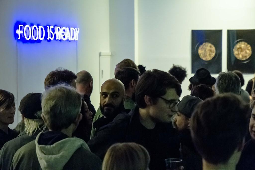 Die zahlreichen Besucher der Ausstellungseröffnung unterhalten sich miteinander im Zentrum der Gallerie.
