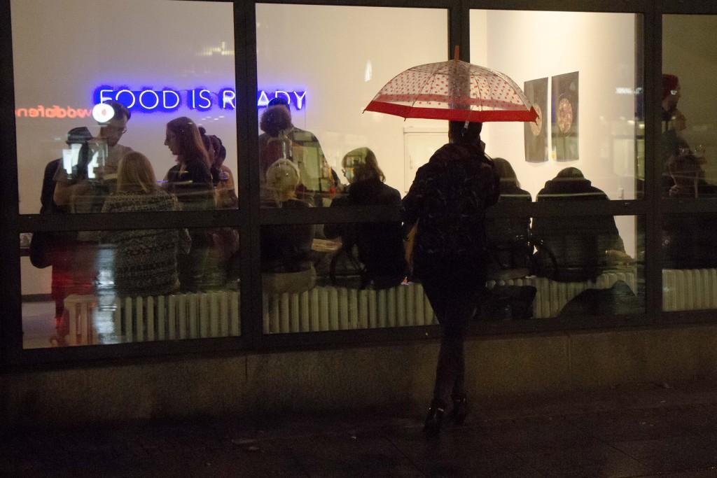 Eine Frau steht unter einem Regenschirm vor der verglasten Galeriefront und schaut ins Innere zu den sich im regen Austausch befindenden Besuchern.